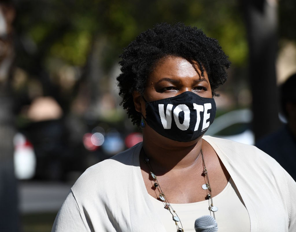 "Stacey Abrams wearing a face mask that says ""VOTE."""