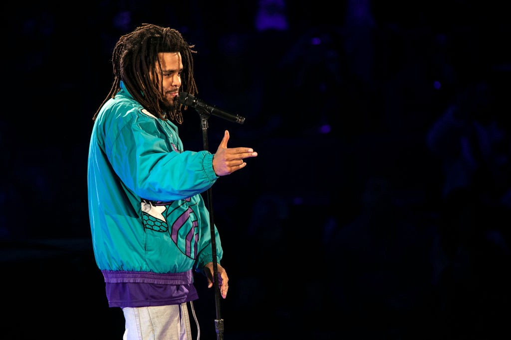 A photo of J. Cole performing on stage.