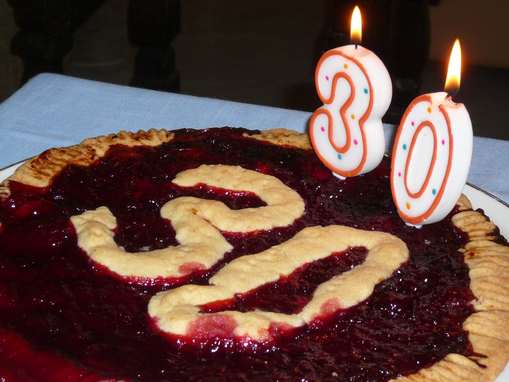 A pie that says 30 on it, and has candles that also show the number 30.