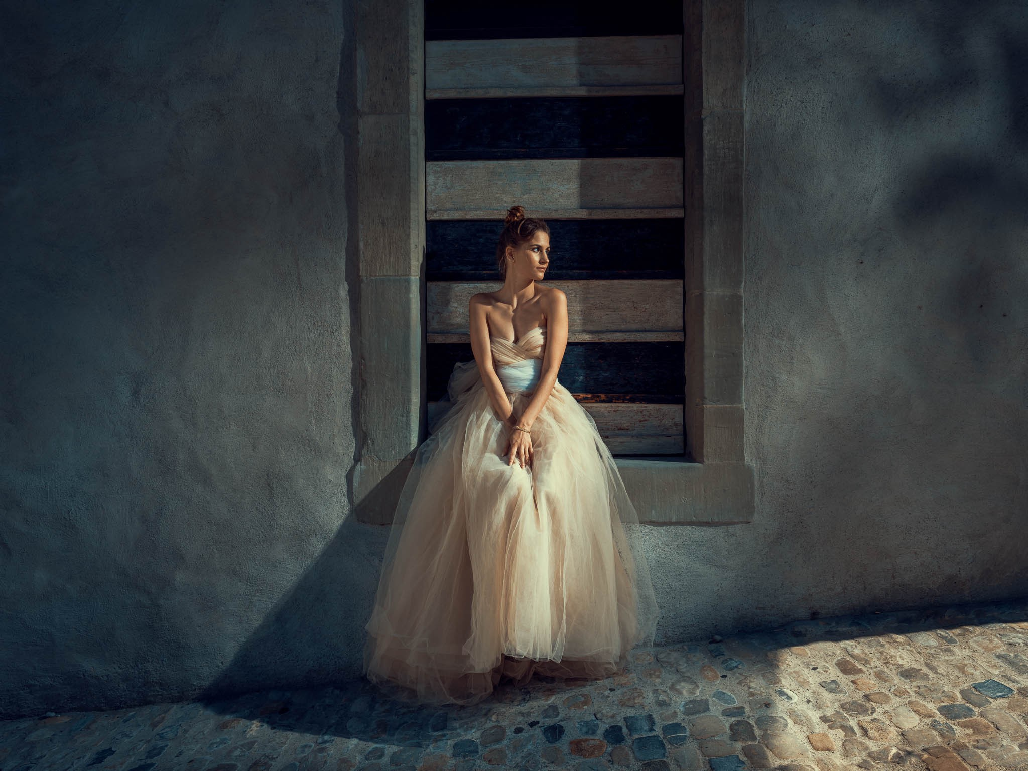 Woman sits and poses in bridal dress for the portrait photographer Damien Lovegrove. RYDE Client.