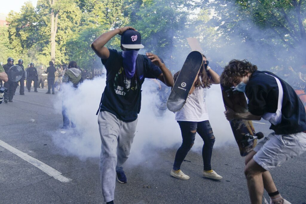 Protesters on Lafayette Square react to smoke canisters and what they believed to be tear gas on June 1.