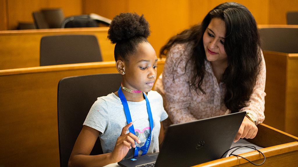 Woman of color in tech showing TechGirlz student how to do something on her laptop.