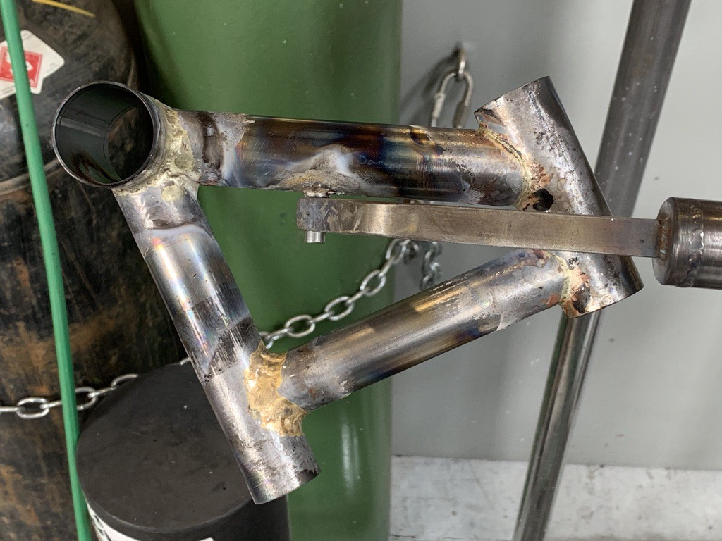 A miniature bicycle frame, roughly welded