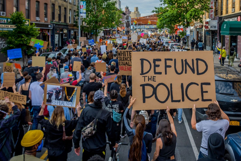 """A photo of a protest. One big sign reads """"DEFUND THE POLICE."""""""
