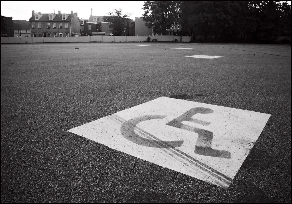 An accessible parking spot in an empty parking lot, in black and white.