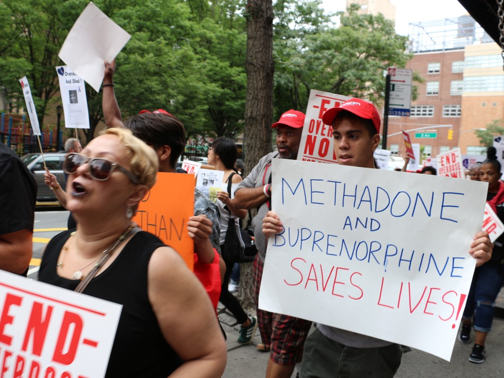 "Protesters stand with signs, large white sign says ""Methadone and Buprenorphine Saves Lives"""