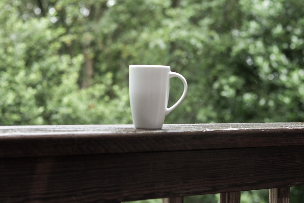 Mug of tea on wooden balcony railing, with forest in background
