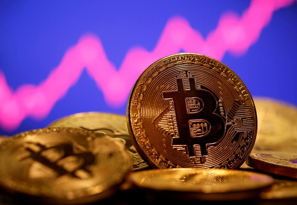 Stock photo of Bitcoin coins in front of a rising stock ticker.