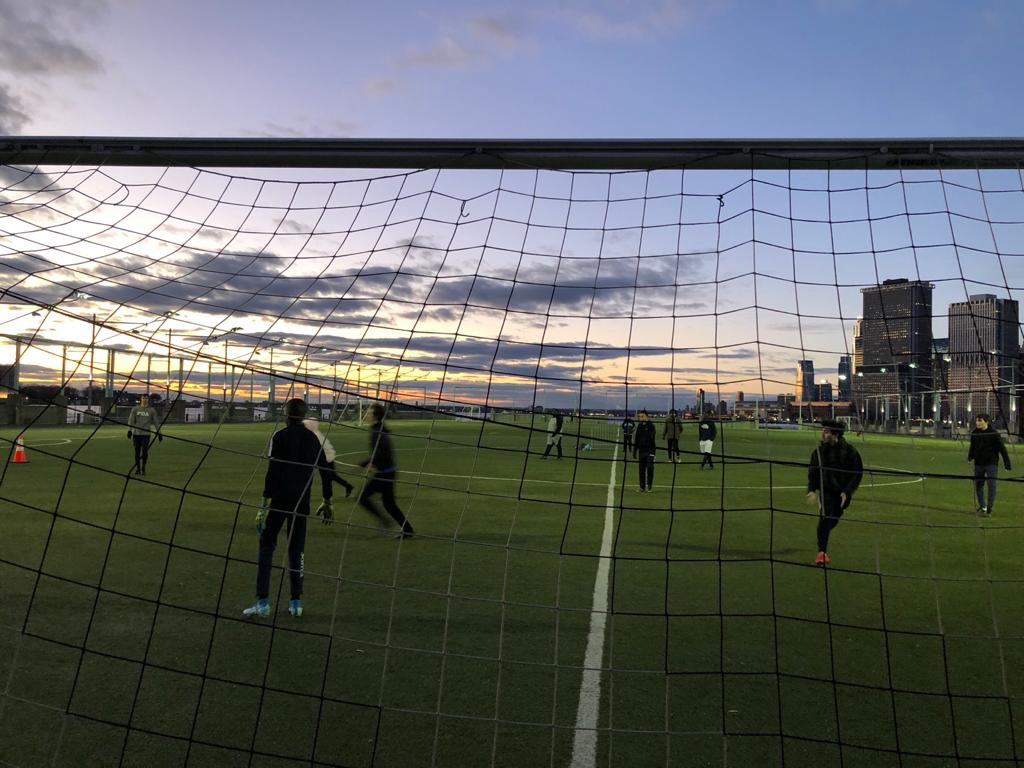 Young men playing soccer in a Brooklyn unaware and serene.