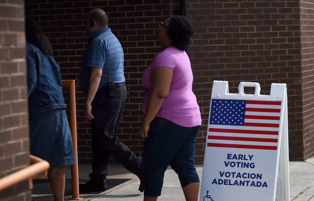 """A photo of three early voters in Florida lining up at a poll. There is a """"EARLY VOTING VOTACION ADELANTADA"""" sign."""