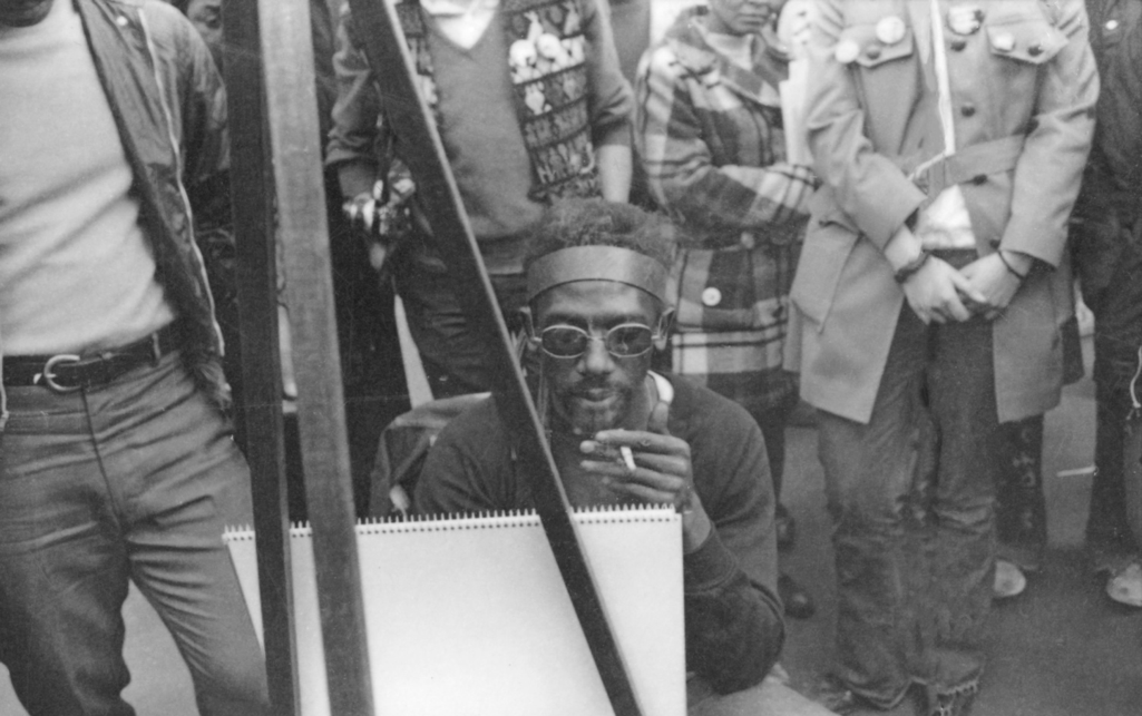 A black man, smoking, focuses on a large art pad in front of him during New York City's first earth day event in 1970.