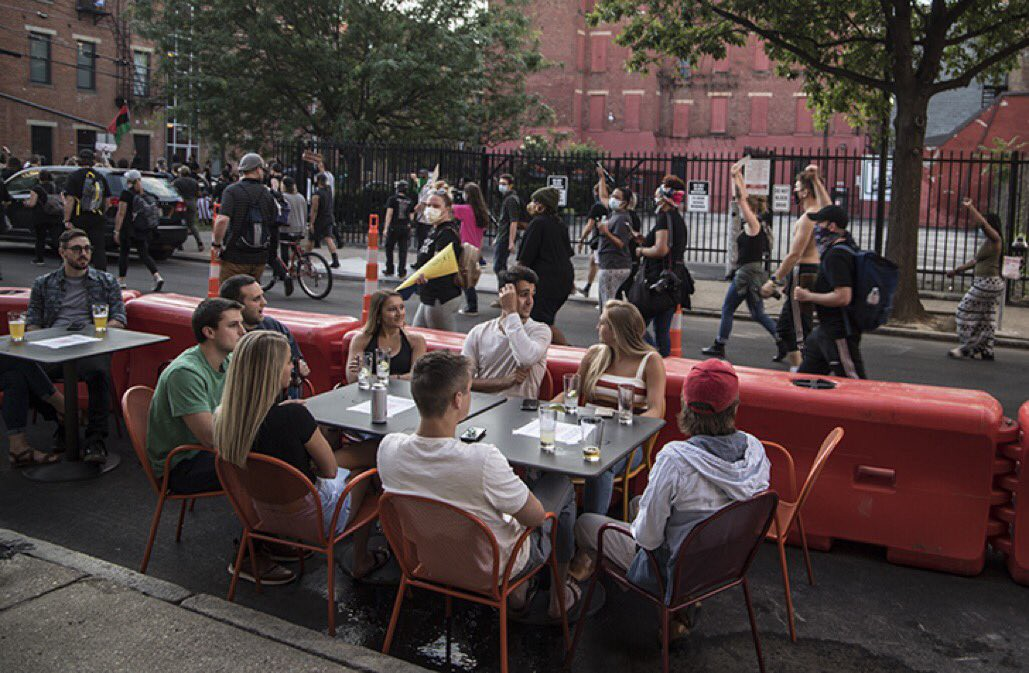 Seven white young people sit at an outdoor dining table as people in a Black Lives Matter Protest march in the street behind them