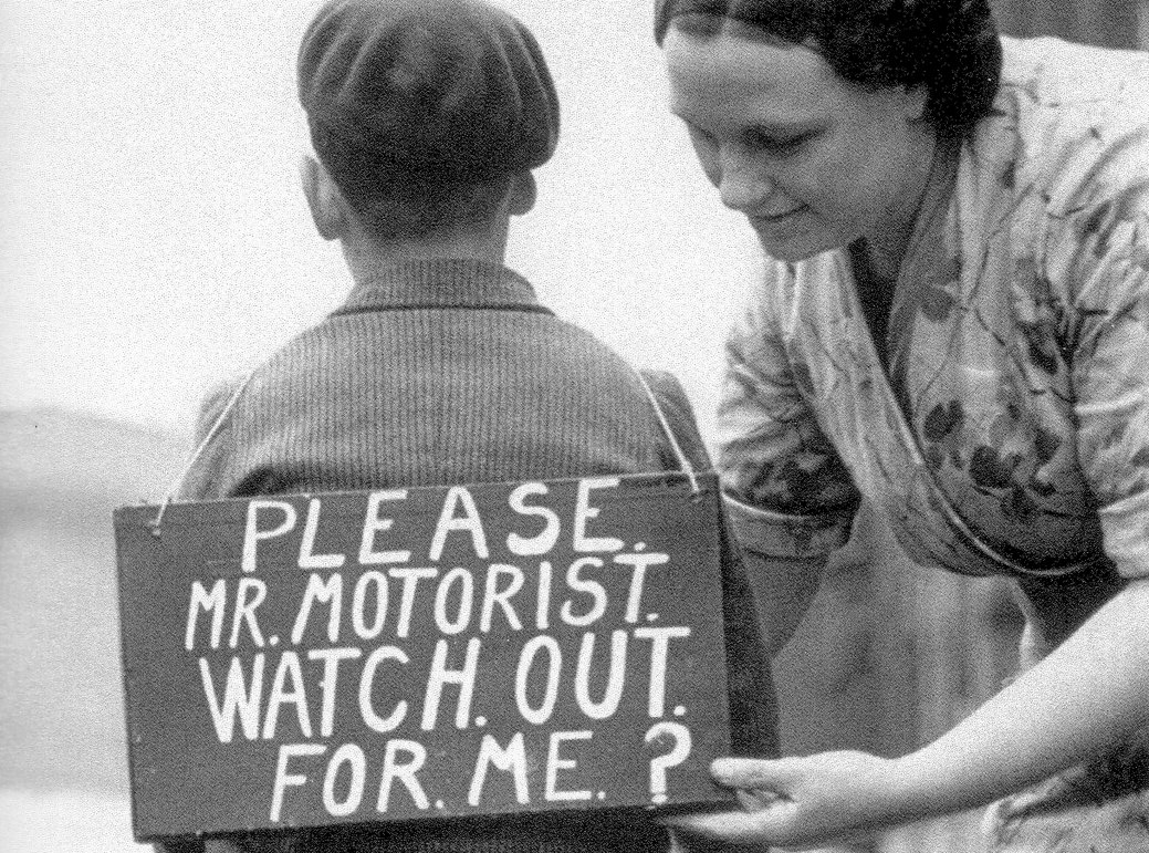 A mother attaches a sign to her son getting ready to ride his bicycle. It reads: 'Please Mr Motorist. Watch out for me?'