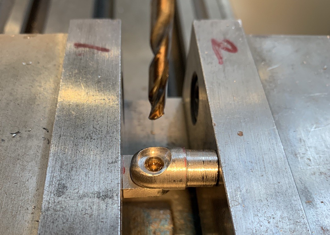 A metal part in the vice of a drill press