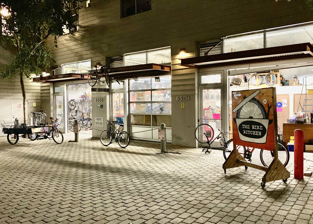 A garage. Some bicycles. A sign that reads 'The Bike Kitchen.'
