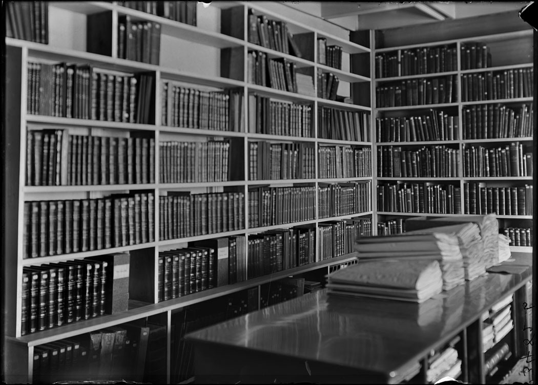 A black and white photograph of library shelves