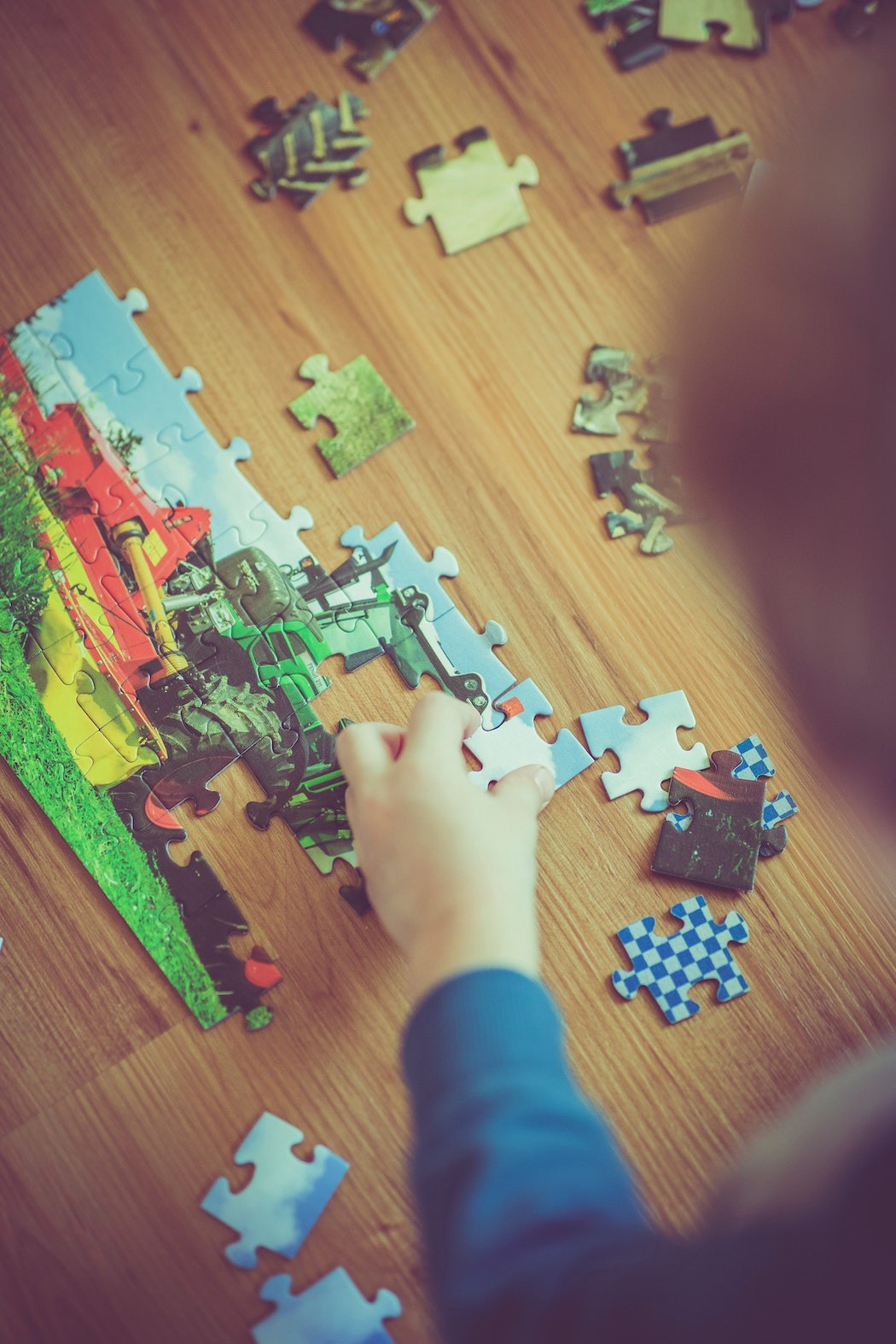 Child fitting pieces of a jigsaw puzzle