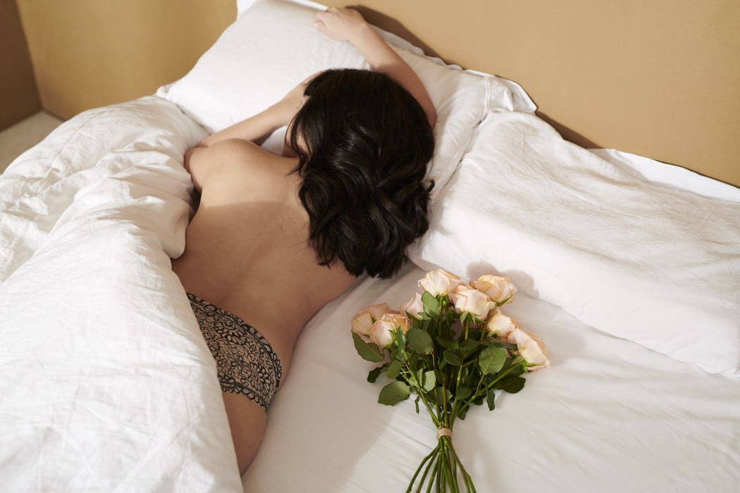 brunette woman laying naked in queen bed with white flowers next to her