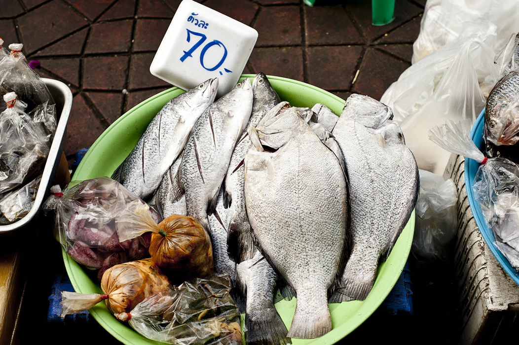 """Inexpensive food for sale at a Koh Samui market. A bowl of fish with a sign that says """"70 baht."""""""