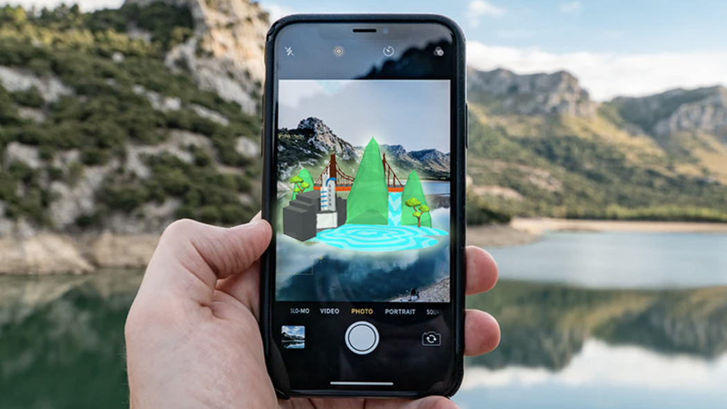 A hand holds up an iphone. The screen shows a mountain lake with 3D augmented reality elements superimposed on it.