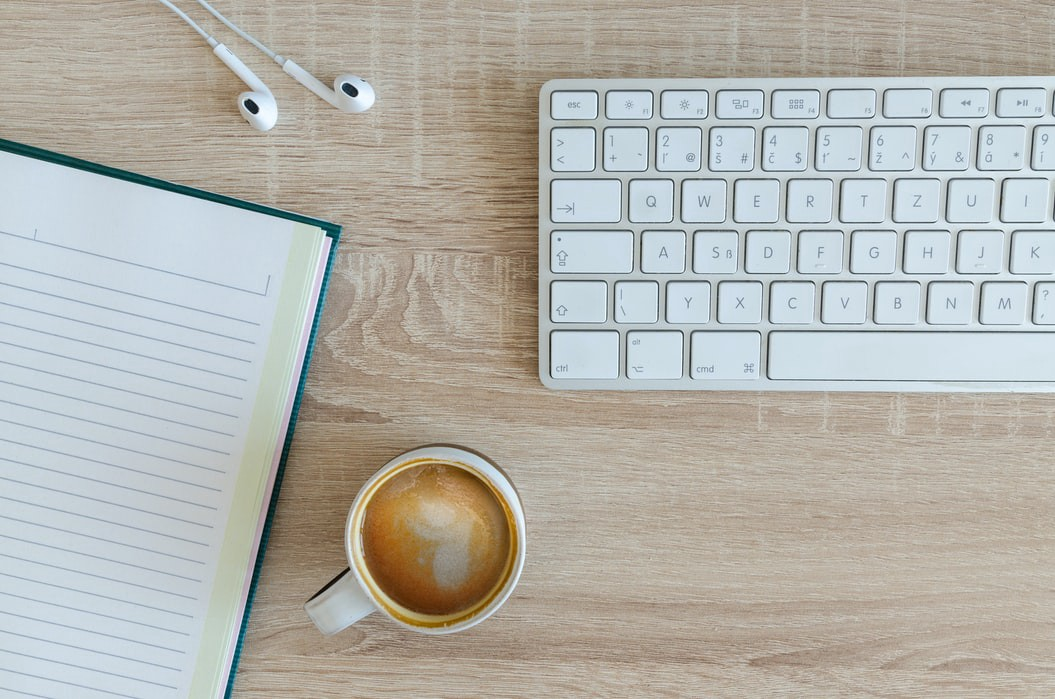 White keyboard, earbuds, lined notebook and mug of coffee places on a wooden surface. The shot has been taken from above, looking down at the objects