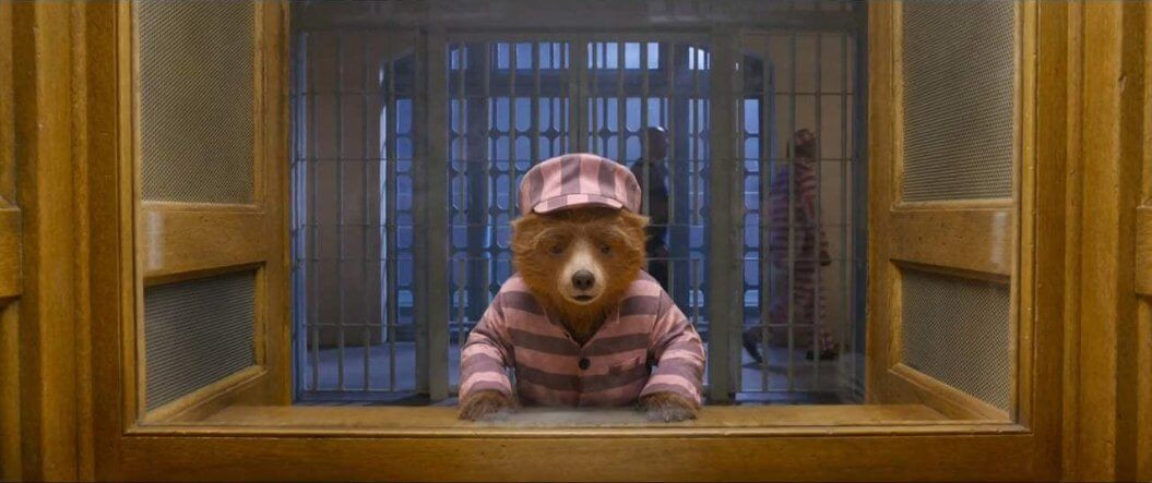 Paddington in a pink prison outfit, leaning over a table.