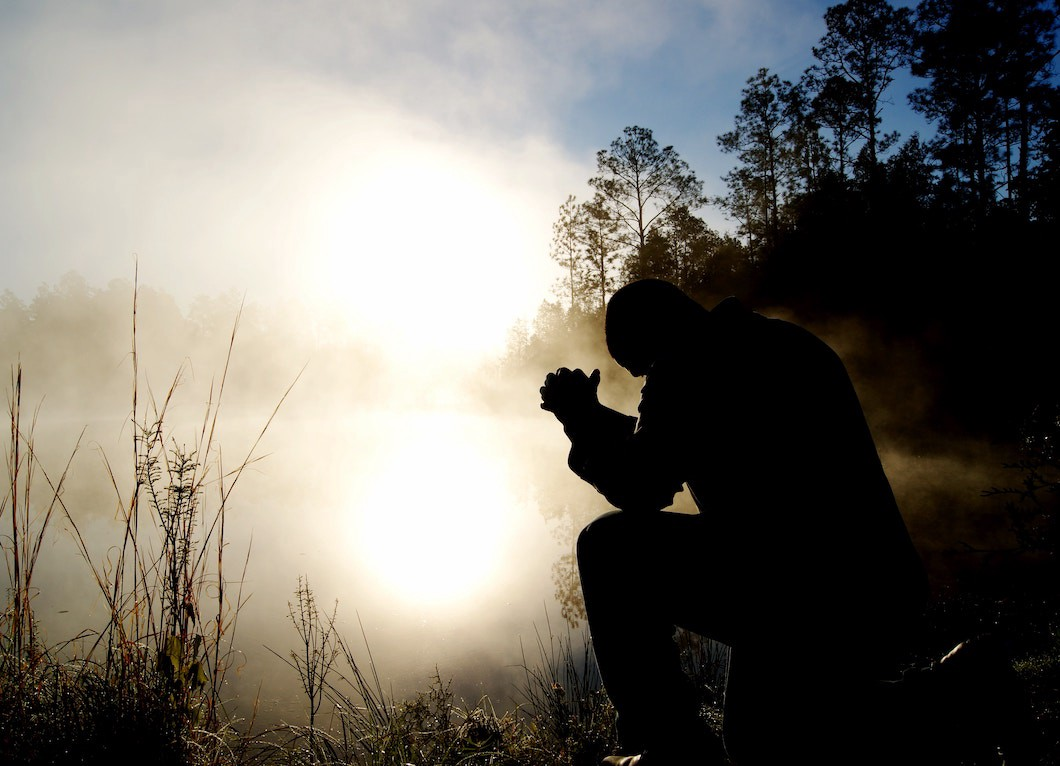 man on one knee next to a pond in the morning sun with hands clasped together praying