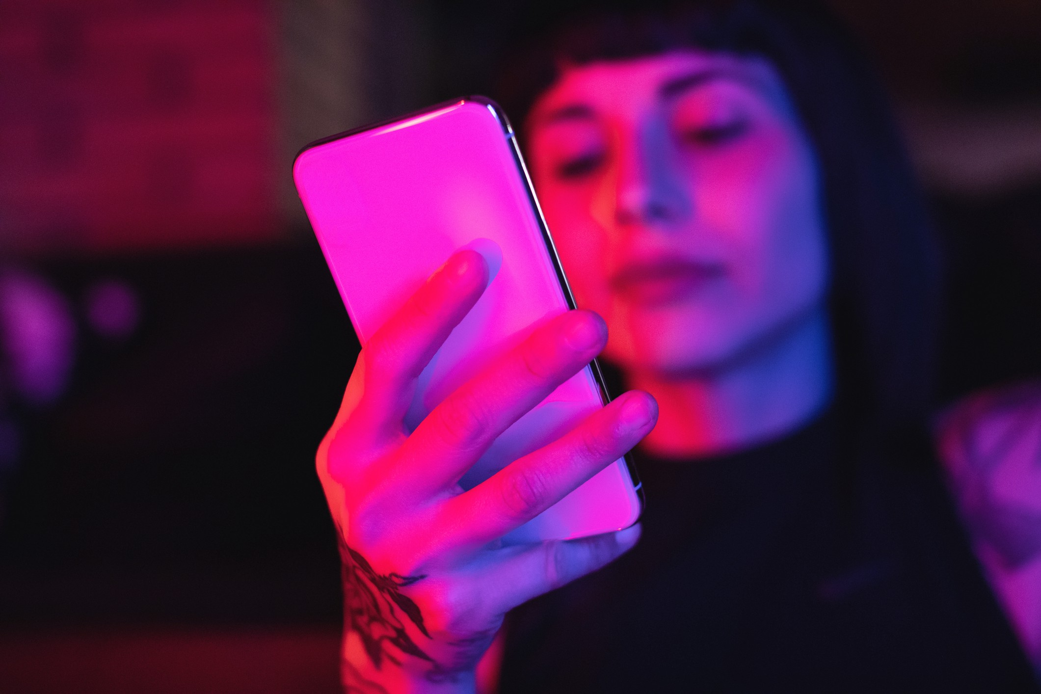 A neon photo of a young woman looking at her white smart phone.