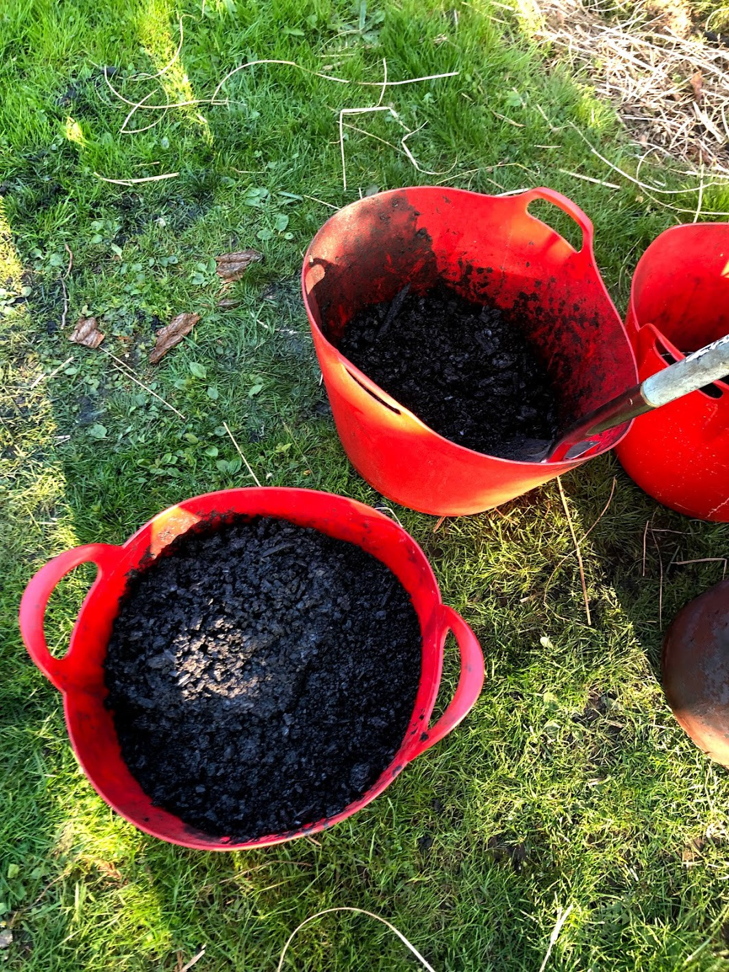 biochar crushed up in red buckets