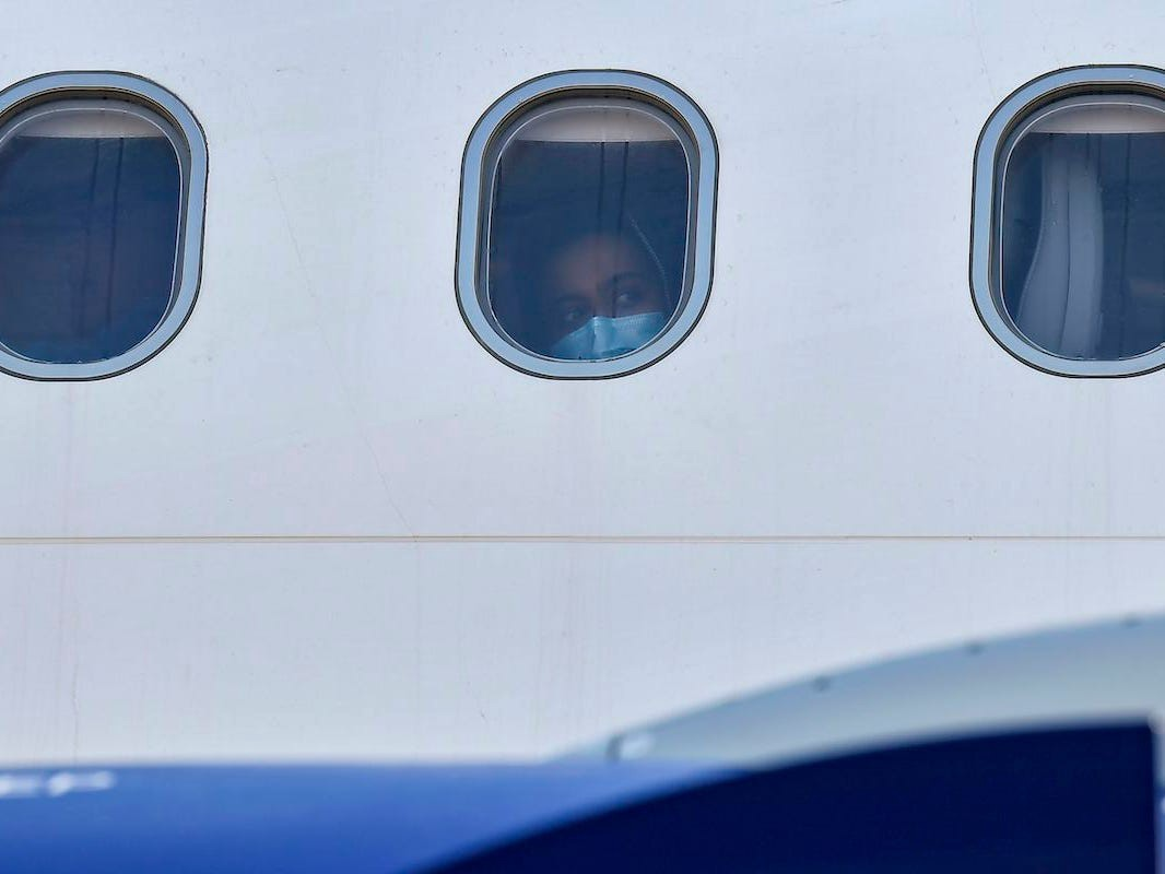 A person peers out the window of a plane.