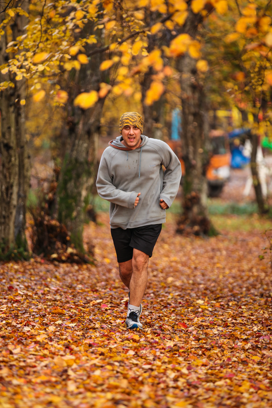 Man running on a path surrounded by trees and fall leaves