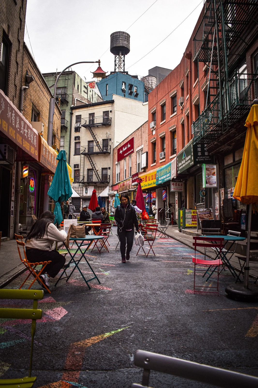 Image of street with tables, chairs, and pedestrians