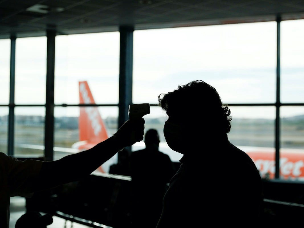 A passenger gets their temperature taken at the airport.