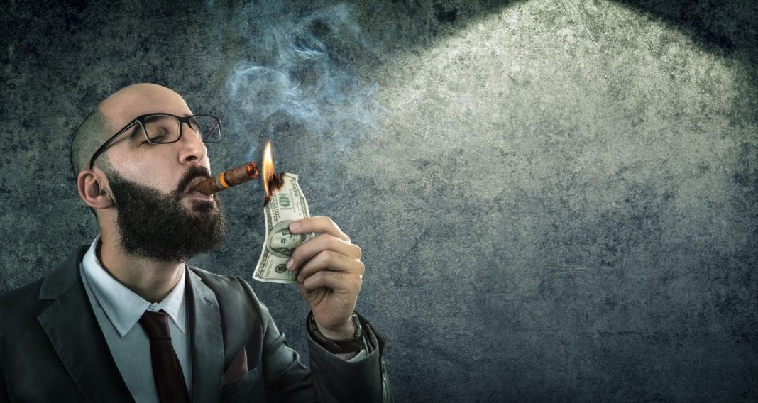 A man in a suit is lighting acigar with a one-hundred dollar bill