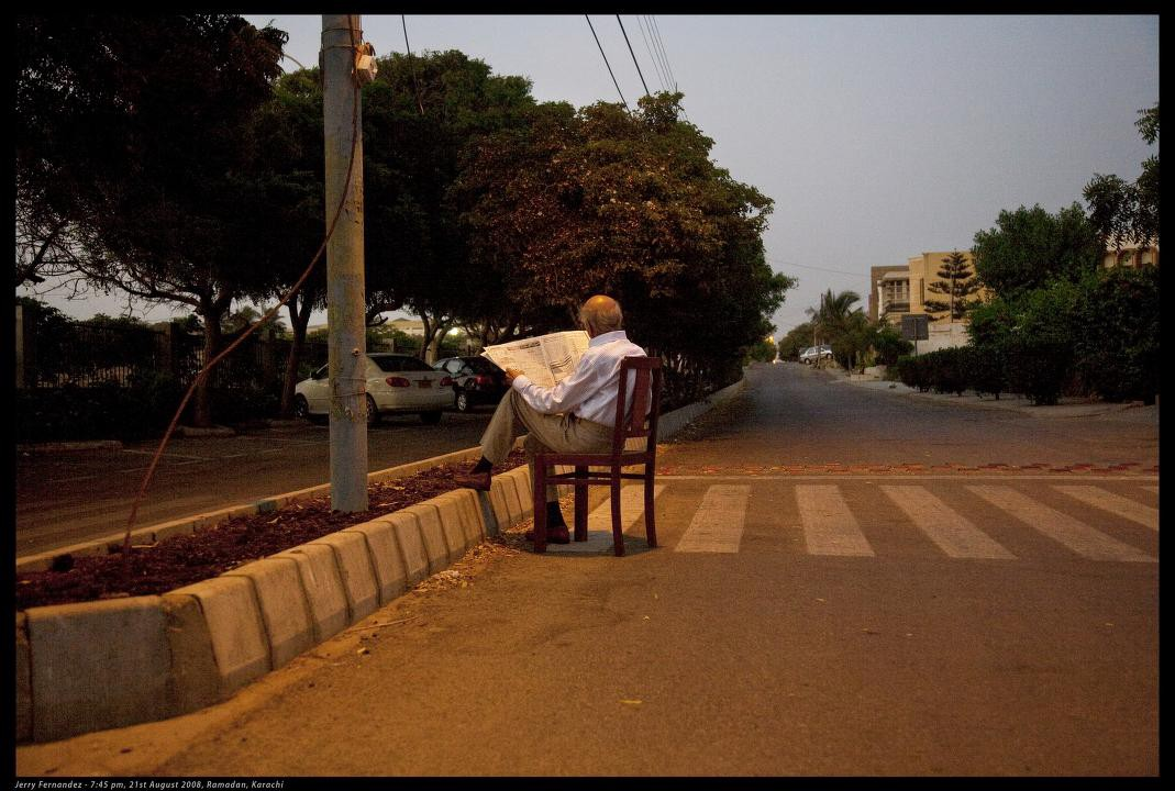 photo of a man sitting on a chair in the street reading a newspaper