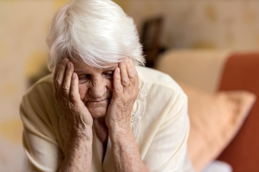 A senior woman with her hands on her face