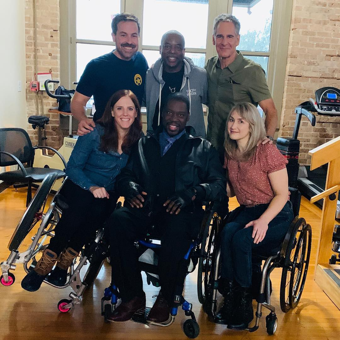 """Six members of NCIS: New Orleans cast and crew pose for a photo. Katherine Beattie, Daryl """"Chill"""" Mitchell, and Teal Sherer Alsaleh sit in the front row while Kurt Yaeger, LeVar Burton and Scott Bakula stand behind them."""