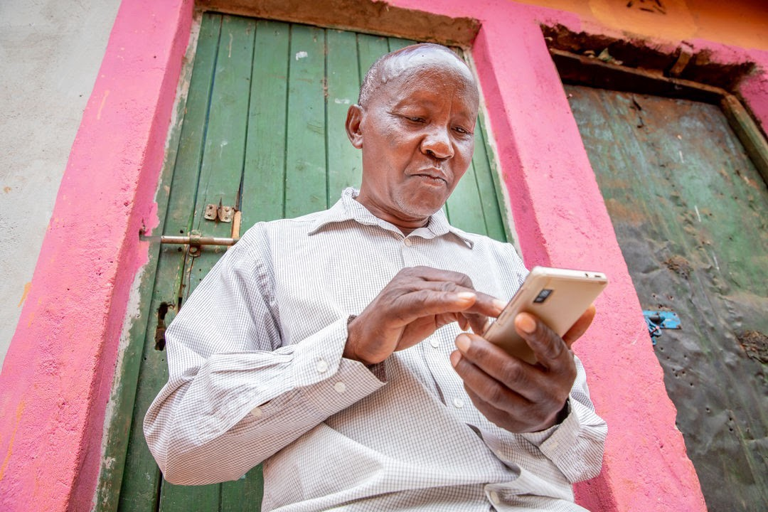 Farmer in Kenya accessing financial services from his phone