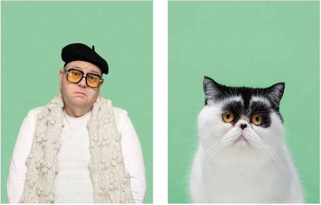 A person with a beret and yellow glasses looks to be shrugging, next to a funny cat with yellow eyes and black head marks