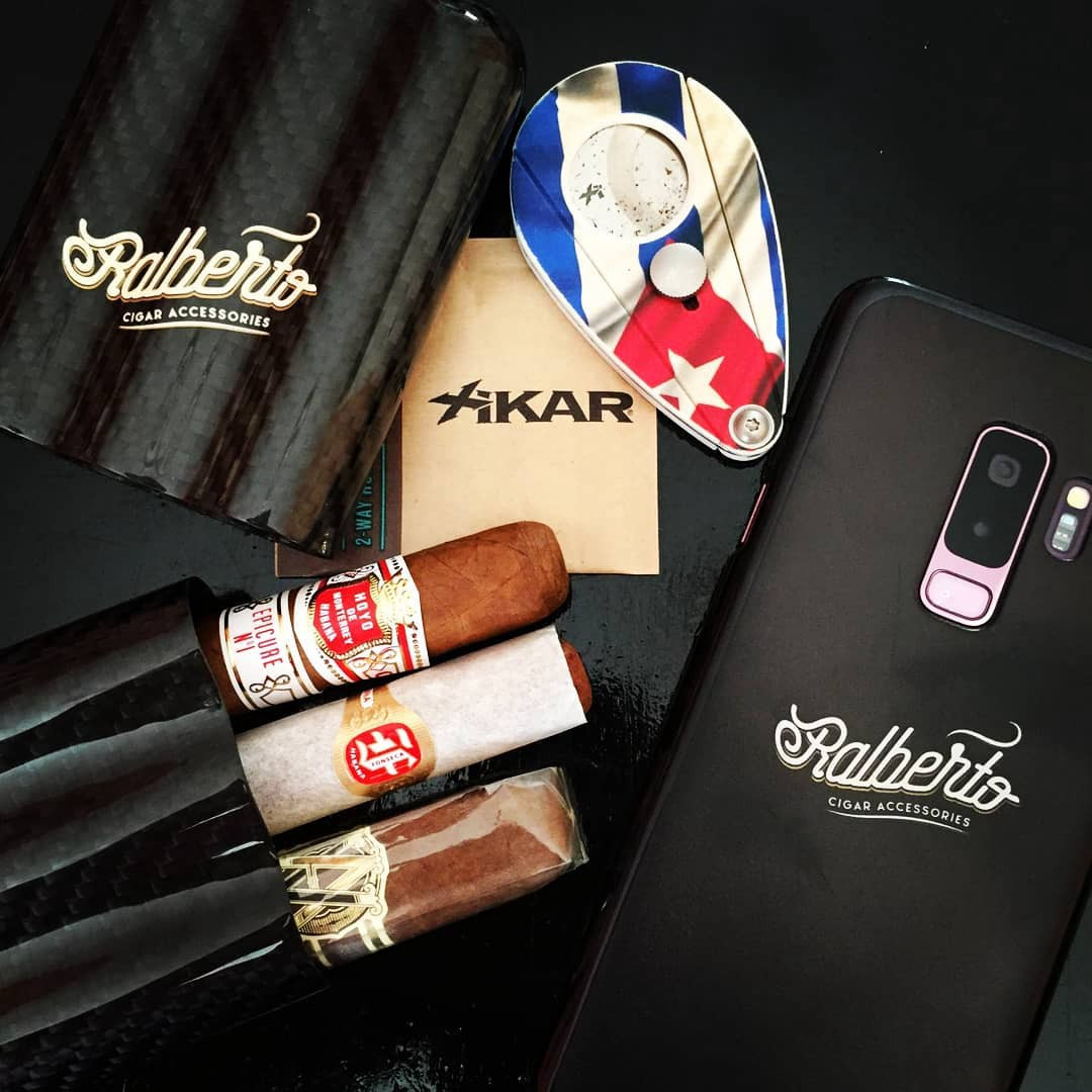 A 3.cigar case next to a cutter with the Cuban flag printed on it. Also, there is also a smartphone with a Ralberto sticker.