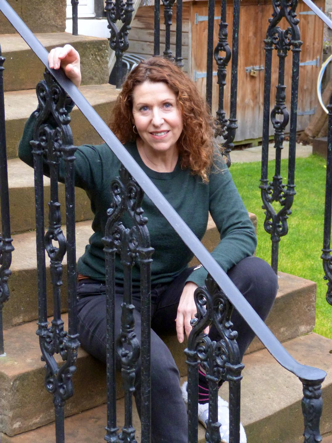 Photo of the writer Meaghan Delahunt sitting on stone steps, one hand resting casually on the wrought iron railing in front of her