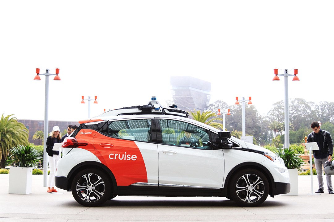 A white Cruise self-driving car is parked outside. The de Young Museum appears in the background, covered by fog.