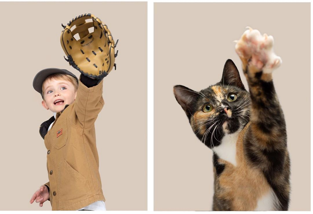 A kid reaches up to catch a baseball with a glove, while a tortoiseshell kitten raises his paw in the air in a similar way