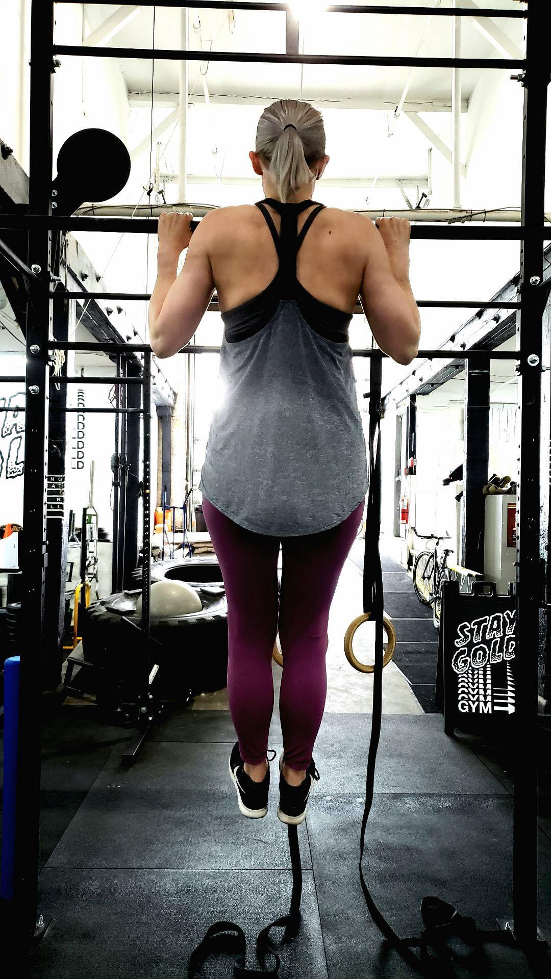 Linn doing an overhand grip flexed arm hang at the top of the bar. She is wearing purple leggings and a grey racer back top.