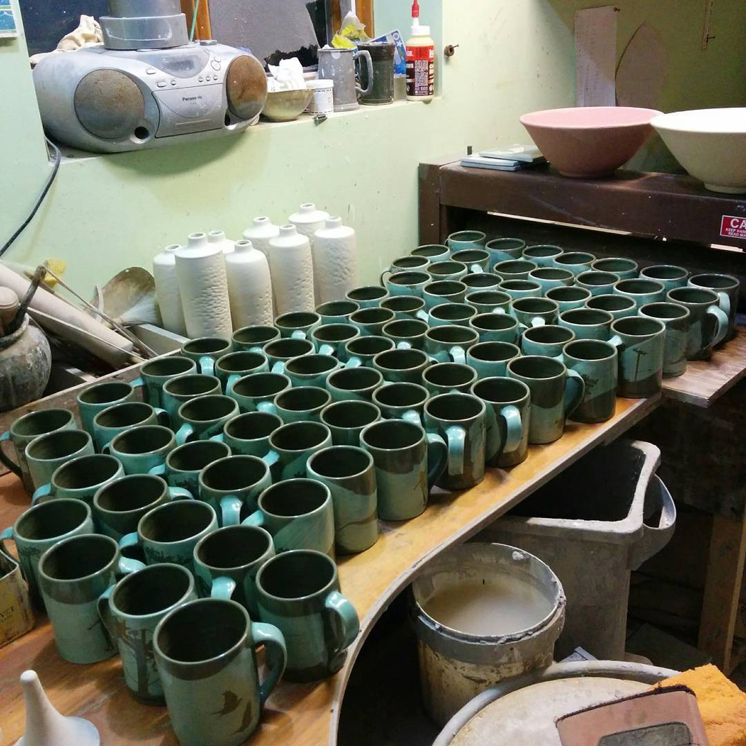 a set of teal mugs in a pottery studio