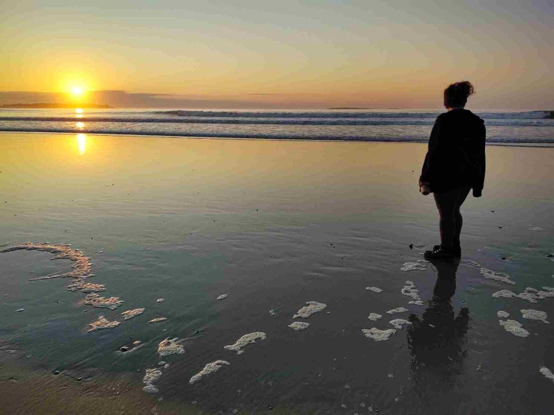 A woman on the beach watches the setting sun on the water.