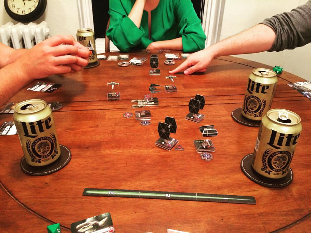 Playing the Star Wars tabletop game X-Wing Minis and drinking Miller Lites with our friends visiting from California.