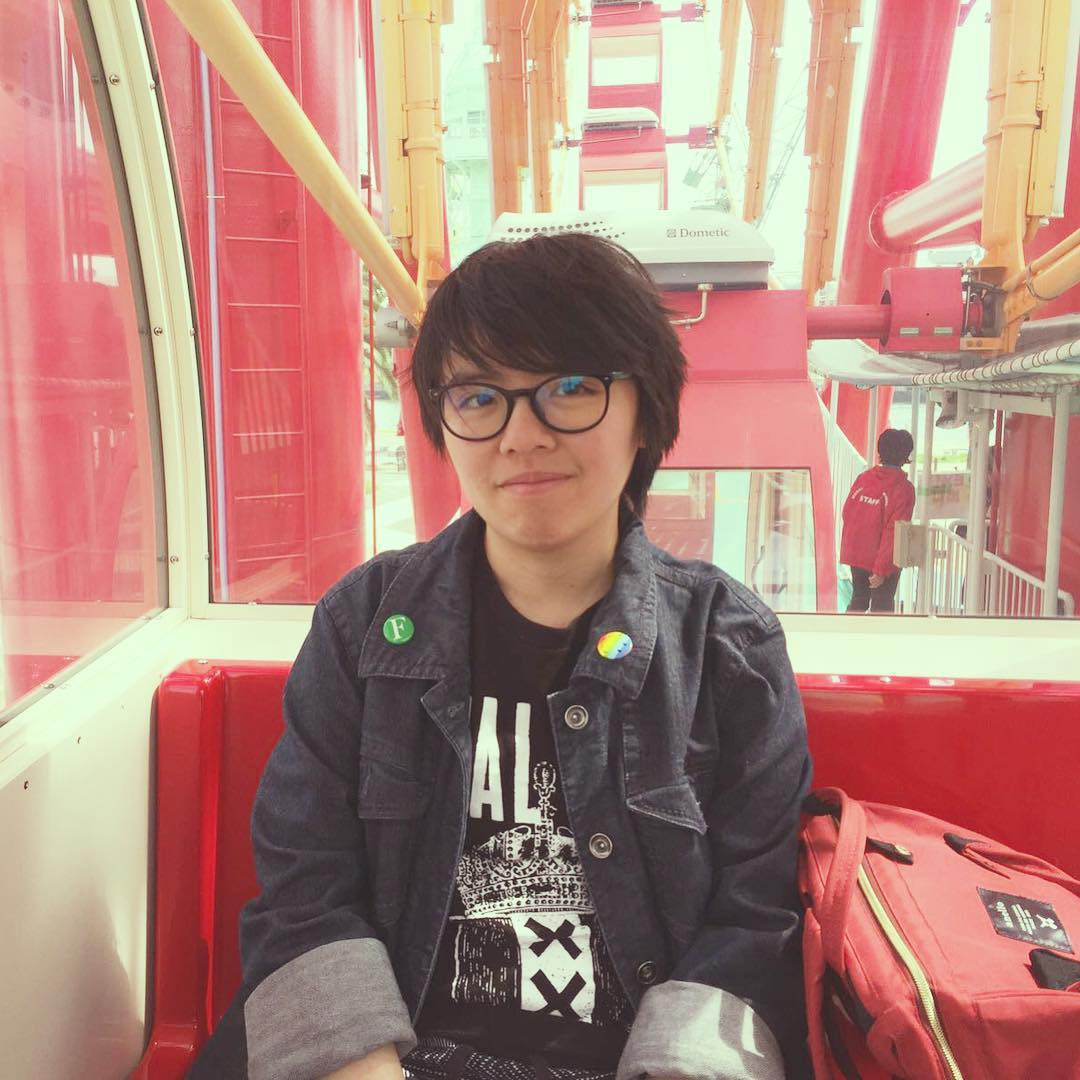 Short haired young Asian woman black glasses, jean jacket, black tshirt, buttons on jacket collar.