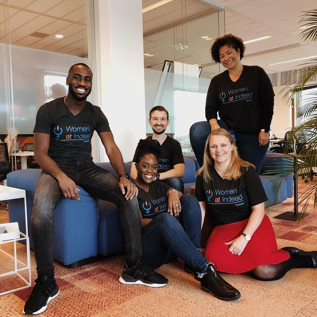 """Image of five Indeed inclusion group members smiling and wearing shirts labeled """"Women at Indeed"""" in a relaxed office setting"""