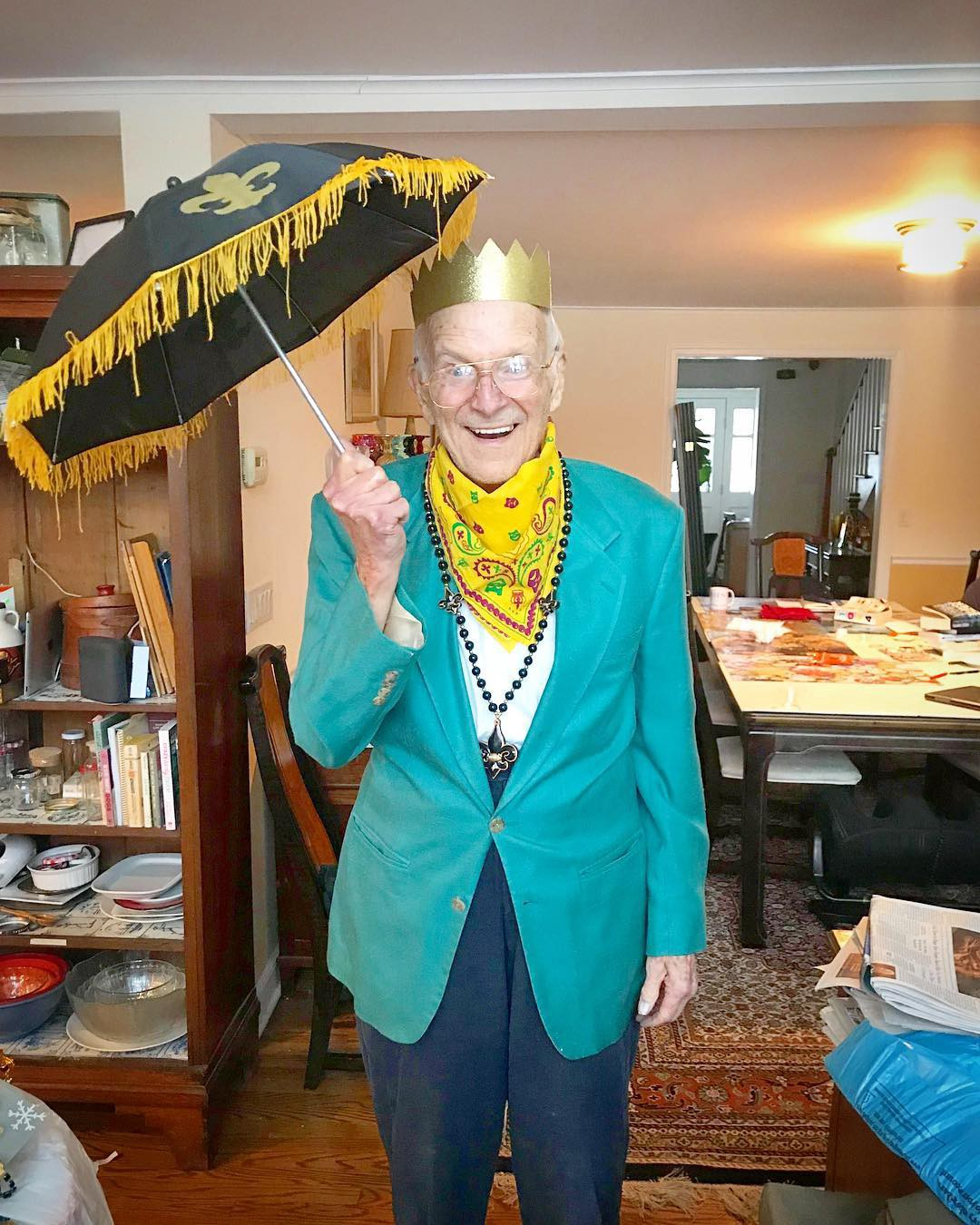Photograph of Alfred holding a tasseled fleur-de-lis umbrella, wearing a crown, beads, a bandana, and a bright green blazer.
